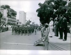 Joseph Kasa-Vubu standing at the stage while looking at the soldiers marching in the street. 1961.