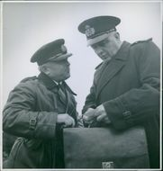 Army Captain standing and talking to each other, holding bag and looking at card. 1939