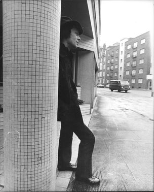 Rock Brynner, son of Yul Brynner, leaning on pillar.