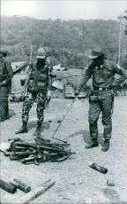Guns on the ground, soldiers standing together and looking at it during Laos war, 1970.
