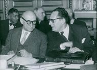Robert Schuman is conversing with his co political friend sitting beside him during a conference.