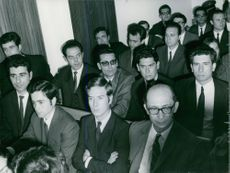 People gathered in a room, sitting down.
