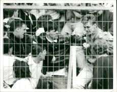 Football hooliganism (a young fan clings for safety)