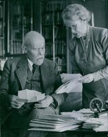 A picture of old woman showing some documents to the old man.