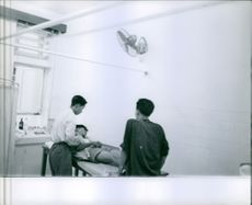 A man lying on the bed, inside the emergency room, with two men standing, assisting him, in Vietnam, 1962.