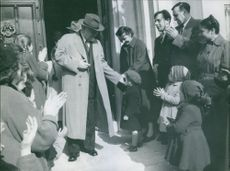 A scene of a Soviet politician, who served as Minister of Defence (1953–55) and Premier of the Soviet Union (1955–58) Nikolai Bulganin pampering child in a crowd of people in front of a building.
