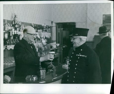 "Where it all began... Mr. Alfred Nurse, land-lord of the public house ""The Orange"" serves a Chelsea Pensioner with his daily glass of beer."