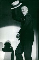 Maurice Auguste Chevalier giving hats off on stage.