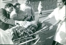 Patient carried by man on stretcher.