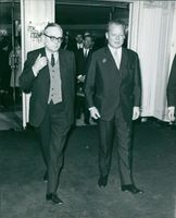 Willy Brandt walking and talking with a man.