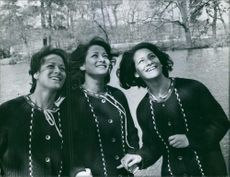 Triplet sisters looking up and smiling.