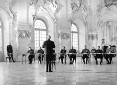 Film scene where a man speaks in front of a group of men.  - 1966