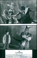 Top: Doug Jones (left) harnesses the strength of metal, as he battles the evil warlord Komodo (Angus Macfadyen). Bottom: Upon his arrival in Tao, Mario Yedidia is regarded suspiciously by Doug Jones, who thinks Mario is in possession of the priceless Manu