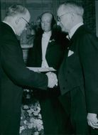Josef Lindqvist handed over a gold medal to Peter Lundqvist at Södertälje's merchant association's 100th anniversary. Behind Erik Erik's view. - 21 March 1948