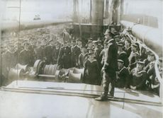 Soldiers standing while looking the soldier standing in the ship during Tyskland war.