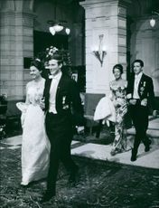 Two man walking with their wife and smiling.