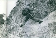 Soldiers climbing over the mountain, holding rope,1960.