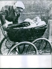 Child in baby cart, woman holding it.