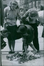 Man and women looking the flowers lying on the floor. 1945