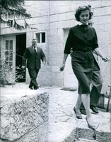 Dr Robert Servatins guiding his wife as they go down a gutter from a house while another man looking at them.