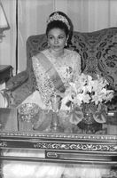 Farah Pahlavi, in gala dress, sitting on sofa.