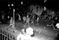 Young people run from police at the riots at the Notting Hill carnival