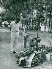 A man looking at a grave.
