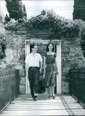 Peter II of Yugoslavia and his wife Alexandra being photographed while walking together with smiling face