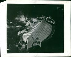 From a movie taping about a ship accident, people wearing life vests trying to climb a capsized boat.