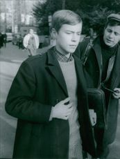 A young boy ignoring the man beside him while walking in the street