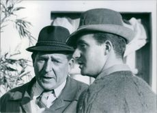 Two men standing together and talking to each other.