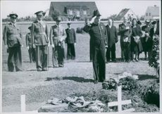People gathered in graveyard during a funeral and saluting. 1943