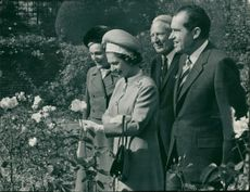 The Queen admiring a rose as she walked yesterday with president