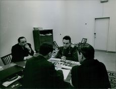 Vladimir Komarov pictured having a discussion with three men.