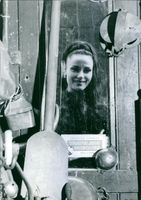 Woman standing beyond a door and smiling.