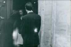 Man and woman standing at the door and talking to woman.