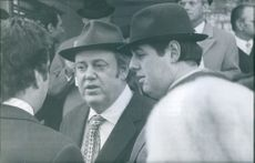 Christopher Soames talking with other people standing next to him during an event.