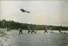 A fighter plane of the U.S. Army Air Forces roars above a detachment of American troops landing on Japanese-held Rendova beach in the Central Solomons of the South Pacific.