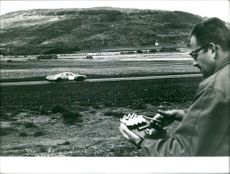 A man monitoring and recording the speed and time of Alpine racing car.