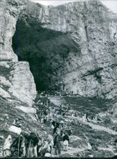 A view of cave with a lot of people walking around. 1967