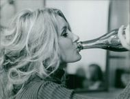 Geneviève Gilles enjoying drink. Photo taken Sep 1969