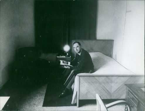 A man sitting on the bedroom while holding a book on his hand.