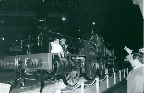 Two young children waves goodbye as they ride a train displayed in a museum.  - Nov 1969