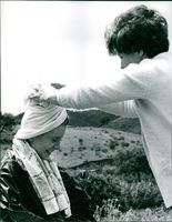 Jane Asher giggling as the woman helps in wrapping the towel on her head.