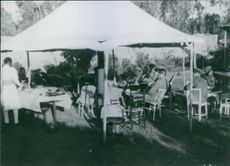 Soldiers siting in the outside a cafe, having breakfast, and talking together.