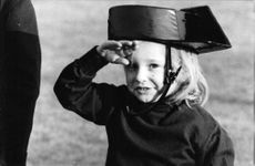 Luis Miguel Dominguín and Lucia Bosé daughter, Paola, making a salute while wearing a hat.