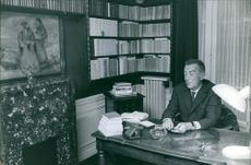 Marcel Aymé sitting at his desk in his office. 1962.