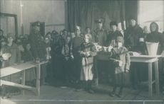 Orphan children standing together, with men and woman.