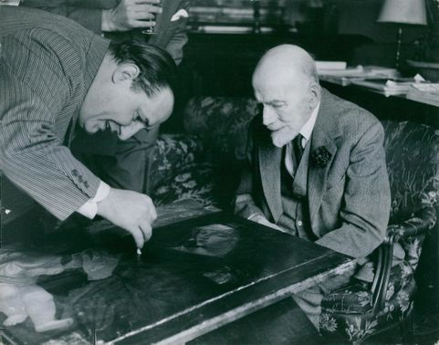 A man showing something in a paint to Bernard Berenson.