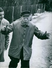 An old man doing some activity, a young man looking at him. 1960
